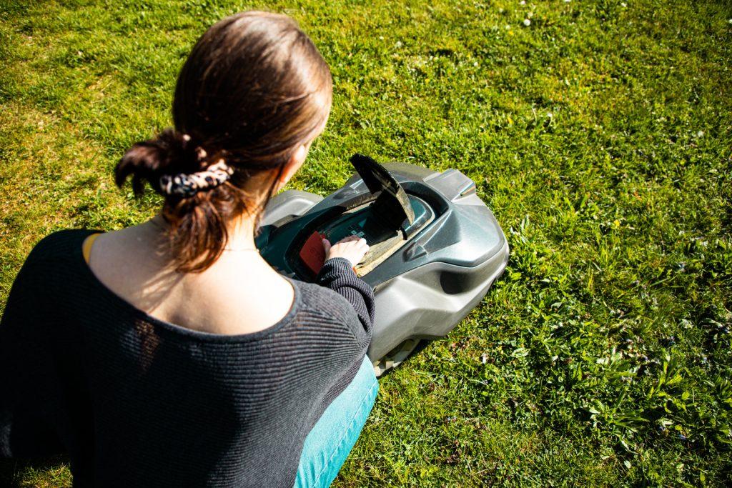 femme qui programme un robot tondeuse